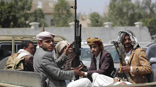 FILE - In this Aug. 22, 2020 file photo, tribesmen loyal to Houthi rebels hold their weapons as they ride in a vehicle.
