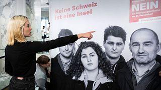 """Laura Zimmerman, co-presidente di Operation Libero, davanti a un poster che dice """"No, la Svizzera non è un'isola"""". Alla fine i favorevoli alla stretta migratoria hanno perso"""