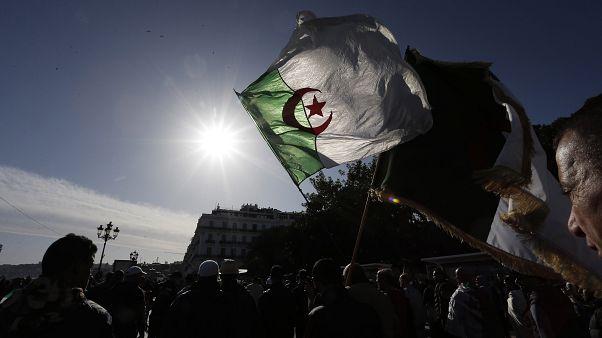 متظاهر يرفع علم الجزائر في احتجاج ضد الحكومة - 20196/12/06