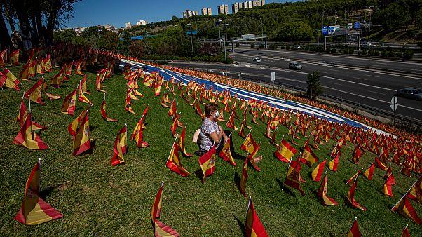 Una mujer se sienta entre las banderas españolas colocadas en memoria de las víctimas del coronavirus en Madrid, España, el domingo 27 de septiembre de 2020.