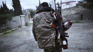 Un combattente di origini armene con dei Kalashnikov a Martakert, nella regione separatista del Nagorno-Karabakh. Foto del 2016