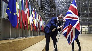 Un membre du protocole retire le drapeau du Royaume-Uni du bâtiment Europa à Bruxelles, le 31 janvier 2020, alors qu'il a mis fin à ses 47 ans d'appartenance à l'UE.