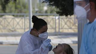 A health worker carries out a COVID-19 test of a resident of Larnaca