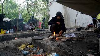 Migrants standing next to makeshift tents inside rundown building on edge of forest