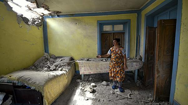 A woman shows damage to her house after shelling on the Armenia-Azerbaijan border in July 2020.