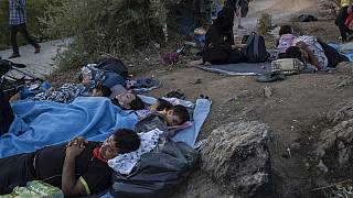 Migrants sleep outside the burned Moria refugee camp, on the northeastern Aegean island of Lesbos, Greece, on Wednesday, Sept. 9, 2020.