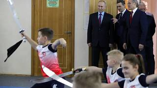 Russian President Vladimir Putin, background left, watches a performance by students of the Martial Arts Centre