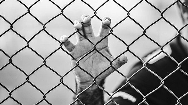 Hand am Drahtzaun