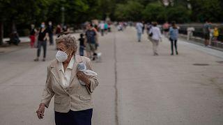 Una anciana, usando una mascarilla para prevenir la propagación del coronavirus, da un paseo en el parque del Retiro en Madrid, España, el lunes 1 de junio de 2020.