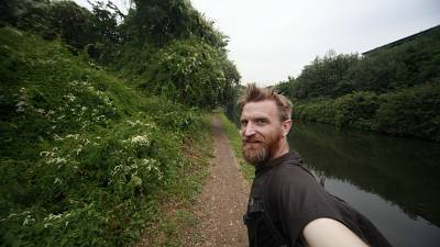 Guerrilla geographer, Daniel Raven-Ellison walking along the side of a canal
