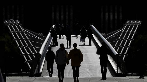 People are silhouetted as they walk over Millennium Bridge in London