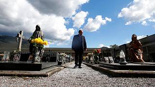 Rev. Mario Carminati walks in a cemetery in Casnigo, near Bergamo, Italy, Sunday, Sept. 27, 2020.