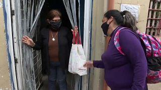 Una voluntaria entrega ayuda alimentaria a una mujer en Buenos Aires