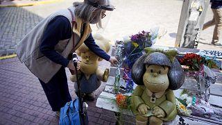 Una mujer deposita un ramo de flores en el banco de Mafalda en Buenos Aires