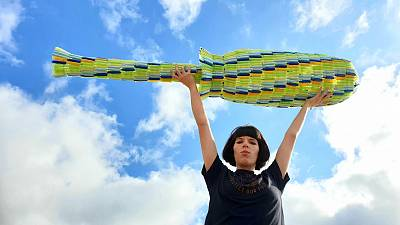 Ella Daish holds her giant 1.8m tampon applicator made from period plastic.