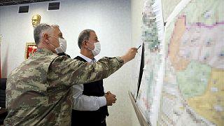وزير الدفاع التركي خلوصي أكار (يمين) وهو ينظر إلى خريطة مع أعضاء قيادة القوات المسلحة التركية خلال اجتماع في مركز التحكم في أنقرة، 17 حزيران / يونيو 2020
