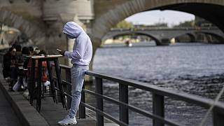A man check his phone at a cafe terrace along the Seine river, Saturday Sept.26, 2020 in Paris.
