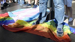 رجل يقف على علم قوس قزح خلال مظاهرة ضد المثليين والمتحولين جنسيا