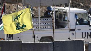 دورية تابعة للأمم المتحدة تمر بجانب علم حزب الله وحاجز إسمنتي في جنوب لبنان على الحدود مع إسرائيل