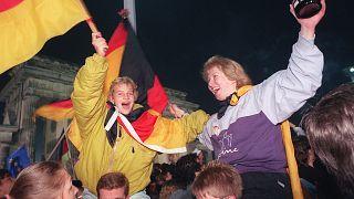 Jóvenes berlinesas ondean banderas alemanas durante la celebración de la reunificación del país en la Puerta de Brandenburgo, Berlín. 3 de octubre de 1990