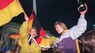 Berliner youths wave German flags during the celebration of the country's reunification at the Brandenburg Gate, Berlin. October 3, 1990