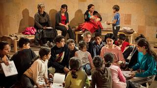 Women and children read books in a bomb shelter as they seek refuge from shelling in Stepanakert/Khankendi, in region of Nagorno-Karabakh. October 1, 2020