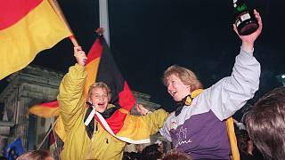 Берлинская молодежь размахивает немецкими флагами, празднуя воссоединение страны у Бранденбургских ворот. 3 октября 1990 года.