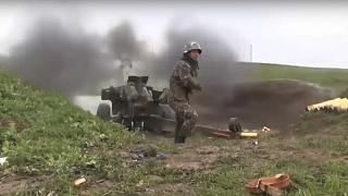 an Armenian serviceman fires a cannon