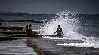 Una mujer habla con dos personas mientras una ola les salpica en La Habana