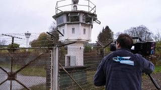 A cameraman films a control tower of the former GDR border guard forces in Moedlareuth prior to the 30th anniversary of the falling of the Berlin wall