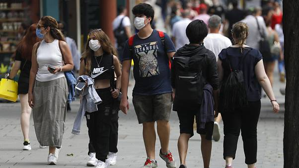 FILE - In this Thursday, Aug. 13, 2020 file photo, shoppers walk along Oxford Street in London.