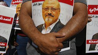 أشخاص يحملون ملصقات للصحفي السعودي جمال خاشقجي بعد مرور عامين على مقتله، بالقرب من القنصلية السعودية في اسطنبول
