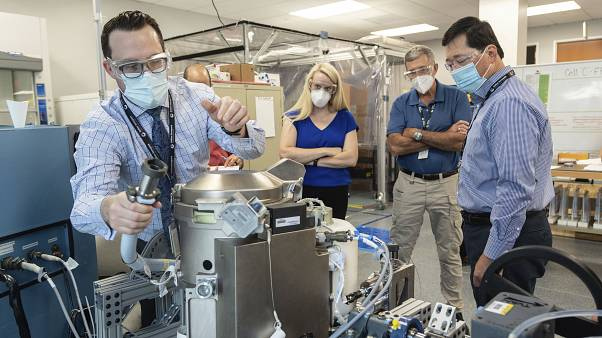 In this June 18, 2020 photo provided by NASA, astronaut Kate Rubins, center, and support personnel review the Universal Waste Management System, a low-gravity space toilet.