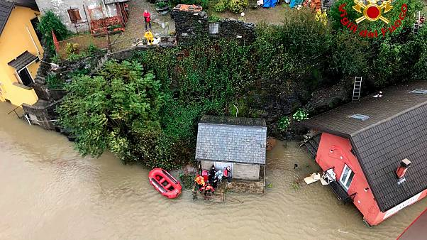 Firefighters evacuate people from a house amidst flooding in the town of Ornavasso