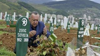 Tarik Svraka visits the graves of his parents in law who died of COVID-19 related complications, in Zenica, Bosnia, Monday, Sept. 28, 2020.