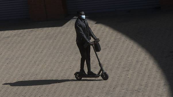 A passenger arrives at Atocha rail station on an electric scooter in Madrid, Spain, Saturday, Oct. 3, 2020.