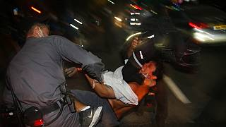Israeli police officers arrest an Israeli protester during a demonstration against lockdown measures that they believe are aimed at curbing protests against Benjamin Netanyahu