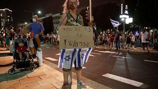 """Una manifestante israelí sostiene una pancarta que dice """"no es un encierro, es un toque de queda político"""" durante la manifestación contra las medidas del confinamiento."""