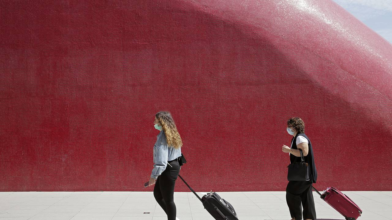 Two women wearing face masks pull their suitcases outside Lisbon's airport, Friday, Sept. 11, 2020
