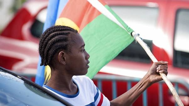 An Independence supporter holds the Kanak flag outside a voting station in the Riviere Salee district of Noumea, New Caledonia, Sunday, Oct.4, 2020
