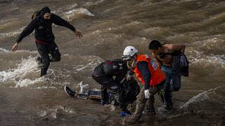 Un grupo de manifestantes socorre al adolescente que quedó tendido y sin conocimiento en el río Mapocho