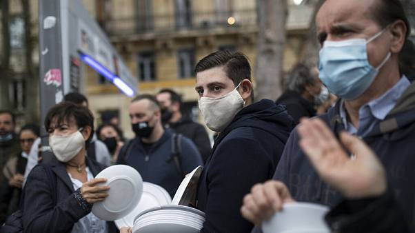 Restaurant and bar owners bang plates together and chant at a demonstration against restaurant and bar closures in Marseille, southern France, Friday Oct. 2, 2020.