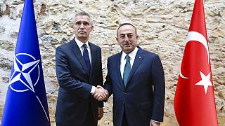 Turkish Foreign Minister Mevlut Cavusoglu, right, shakes hands with NATO Secretary General Jens Stoltenberg