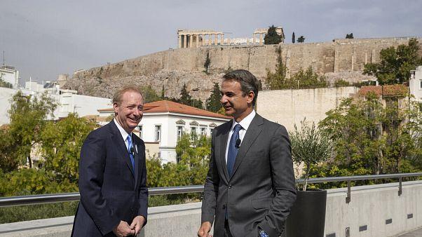 Microsoft President Brad Smith, left, speaks with Greek Prime Minister Kyriakos Mitsotakis