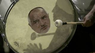 A protester beats a drum showing a portrait of Bulgarian Prime Minister Boyko Borissov during an anti-government protest in front of the new National Assembly building, in Sof