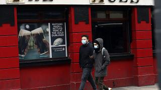 Menschen mit Gesichtsmasken vor einem Pub in Dublin, 16.03.2020