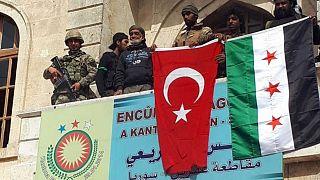 ارتش آزاد سوریه با پرچم مخالفان دولت اسد و پرچم ترکیه پس از تصرف شهر کردنشین عفرین