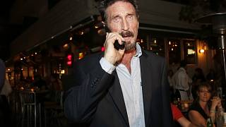 John McAfee pictured in 2012 on his mobile phone in the South Beach area of Miami.