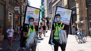 Dos voluntarios ofrecen mascarillas obligatorias en Ámsterdam