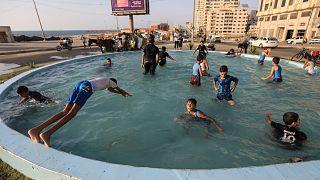أطفال يسبحون في إحدى نوافير غزة
